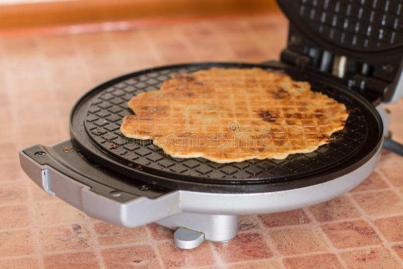 Homemade waffles in a waffle iron royalty free stock image