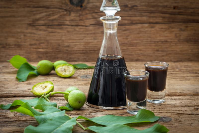 Homemade wallnut liquer on rustic wooden background royalty free stock photo