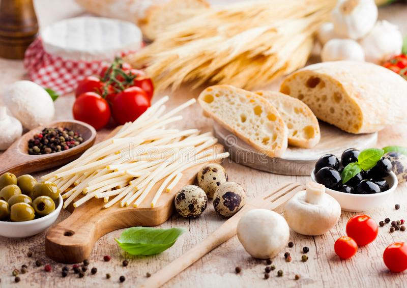 Homemade wheat bread with quail eggs and raw wheat and fresh tomatoes on wooden background. Classic italian village food. Garlic, stock photos