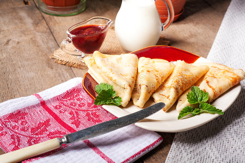 Homemade wheat crepes or pancakes with strawberry jam or marmalade stacked on a plate on a wooden rustic table stock images