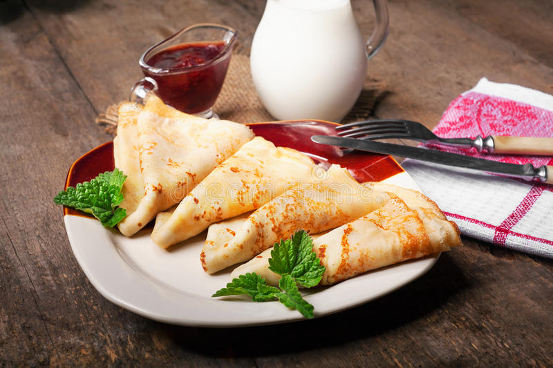 Homemade wheat crepes or pancakes with strawberry jam or marmalade stacked on a plate on a wooden rustic table stock photos