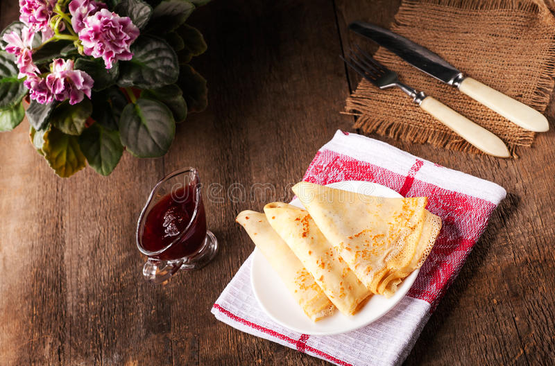 Homemade wheat crepes or pancakes with strawberry jam or marmalade stacked on a plate on a wooden rustic table royalty free stock image