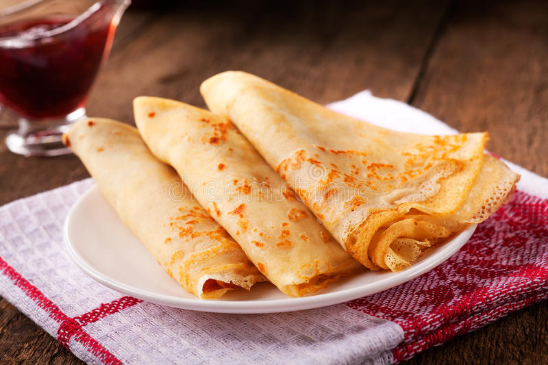 Homemade wheat crepes or pancakes with strawberry jam or marmalade stacked on a plate on a wooden rustic table stock photography