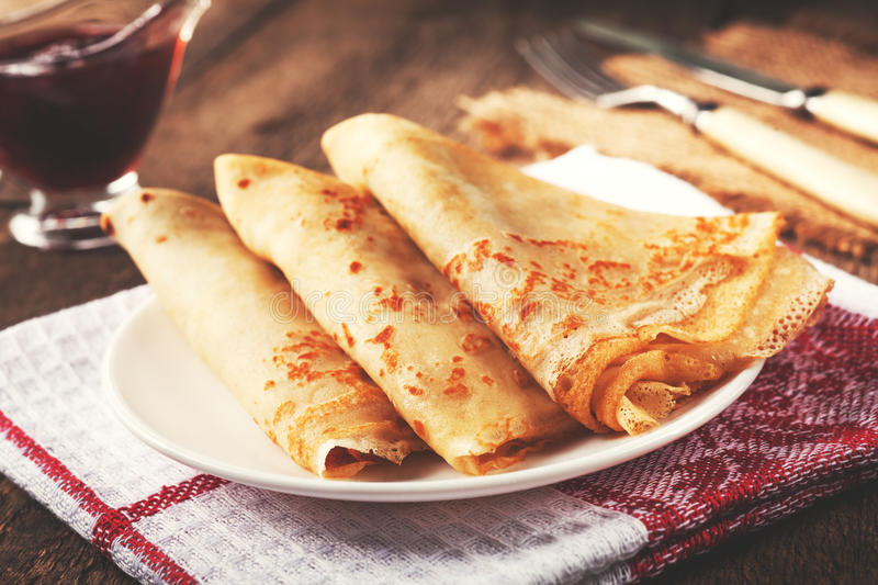 Homemade wheat crepes or pancakes with strawberry jam or marmalade stacked on a plate on a wooden rustic table stock image