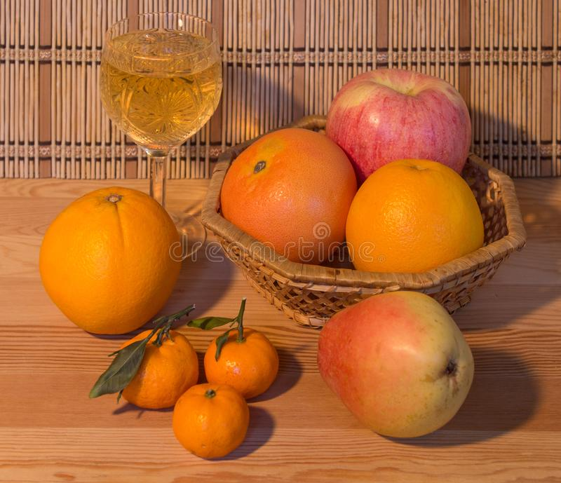 Homemade white wine and ripe fruit on a wooden table. stock image