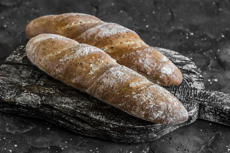 Homemade whole-grain baguettes with provencal herbs on rustic wooden board, on a dark background. Homemade whole-grain baguettes with provencal herbs on rustic royalty free stock photos