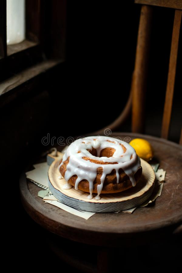 Homemade whole lemon bundt cake with white glaze on top stands on wooden board on old wooden chair stock image