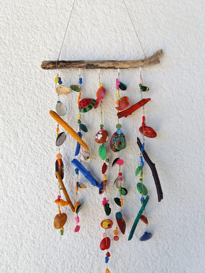Homemade Wind Chimes from seashells with lovely colorfull touch of children. Painted shells, driftwood, some other parts for decoration, hanging on rope with royalty free stock photos