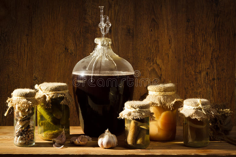 Homemade wine in larder with vegetables royalty free stock photography