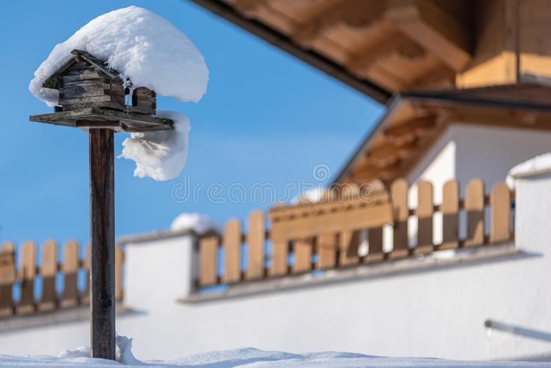 Homemade wooden bird`s feeder in winter under snow. The blu sky. royalty free stock image