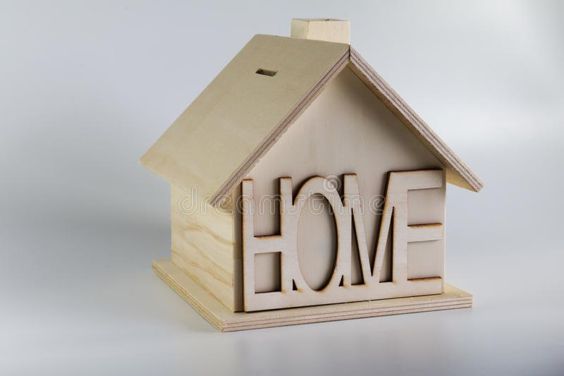 Homemade wooden house piggy bank with the inscription home royalty free stock photos