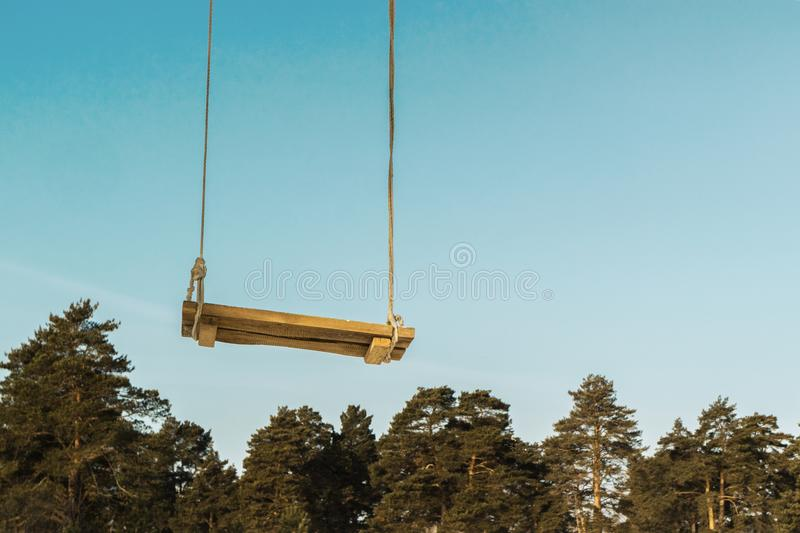 Homemade wooden swing against the blue sky and trees, dreams sweeping to the sky stock image