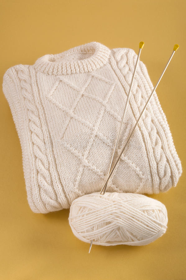 Homemade woolen sweater with Aran cable pattern. Knitwear of a homemade woolen sweater with a pattern of Aran cables and a ball of wool and knitting needles on a royalty free stock image