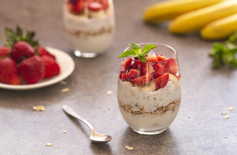 Homemade yogurt parfait with granola, strawberries, bananas and Chia seeds in glasses. Diet dessert with yogurt. Homemade yogurt parfait with granola stock images
