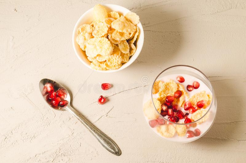 Homemade yogurt with pomegranate and flakes in glass/homemade yogurt with pomegranate and flakes in glass and flakes in a bowl on. A white stone table. Top view royalty free stock images
