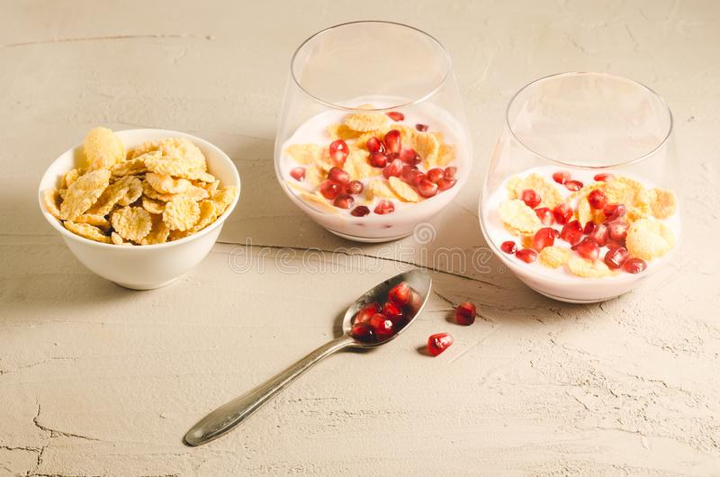 Homemade yogurt with pomegranate in glass and a bowl of flakes/homemade yogurt with pomegranate in two glass and a bowl of flakes. On a white stone background stock images