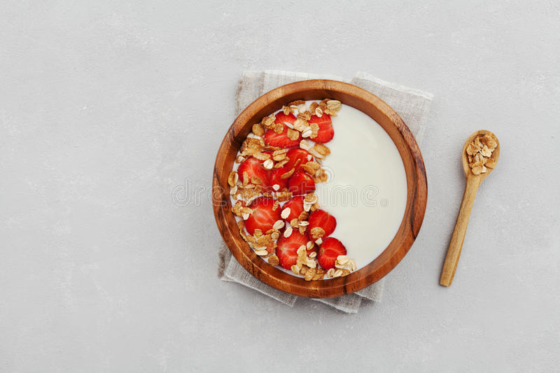 Homemade yogurt in wooden bowl with strawberry and granola or muesli on light table, healthy breakfast from above stock image
