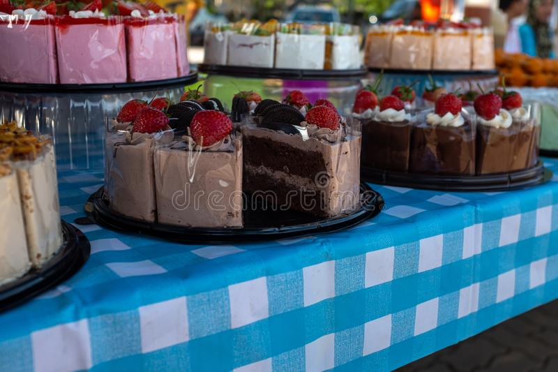 Homemade yummy looking cakes for sale at a Farmers Market, the foreground being chocolate royalty free stock photos