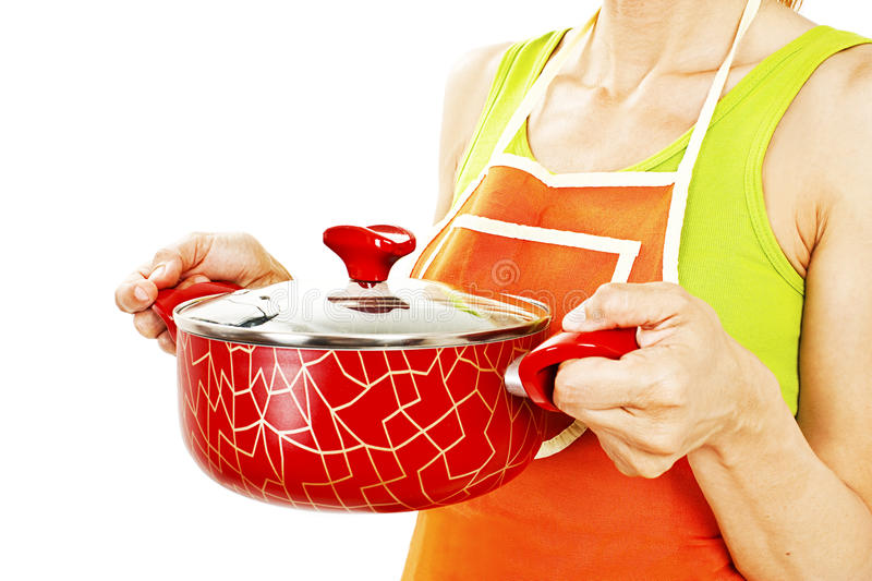 Homemaker in an apron holding pan with ready meal, soup royalty free stock image
