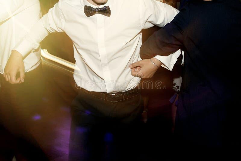 Homens à moda que têm o divertimento e que dançam no partido no restaurante, recep imagens de stock
