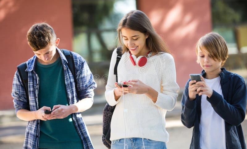 Homens adolescentes e menina que enterram com telefones celulares foto de stock royalty free