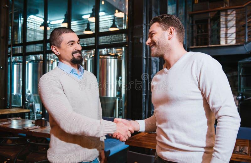 Homens agradáveis deleitados que agitam as mãos foto de stock royalty free