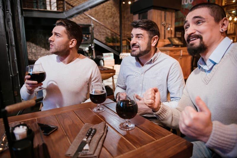 Homens agradáveis deleitados que olham o jogo de futebol foto de stock