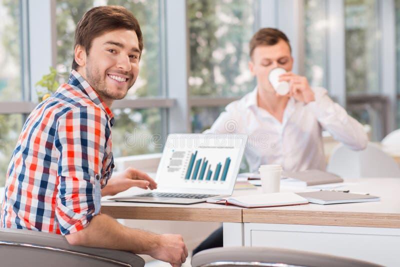Homens alegres que sentam-se na tabela foto de stock