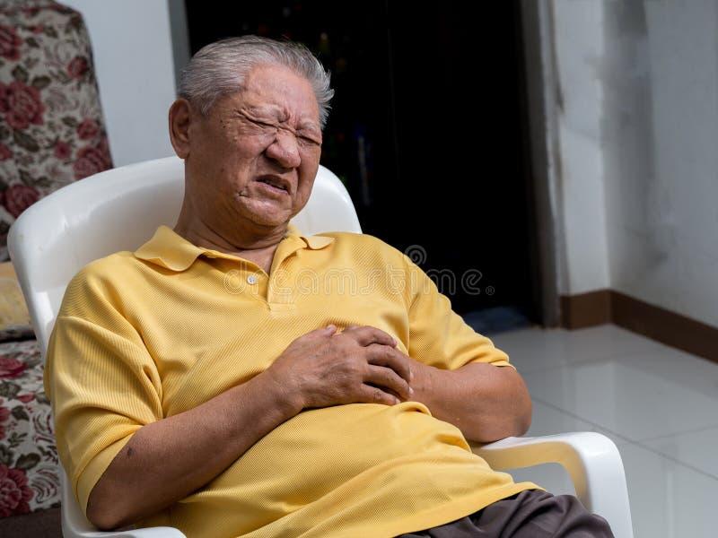Homens asiáticos mais idosos que sentam-se em uma cadeira na sala de visitas com cardíaco de ataque Ambas as mãos do ` s do anciã fotografia de stock