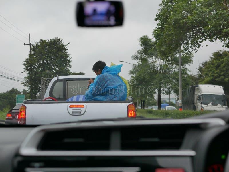 Homens asiáticos que sentam-se na parte de trás de um camionete sem a segurança imagem de stock