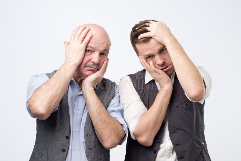 Homens cansados Annoyed que inclinam a cara disponível e que olham indiferentes na câmera, posição furada imagens de stock royalty free
