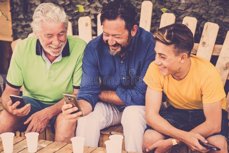 Homens caucasianos dos povos da família completa que sentam-se em um banco do wodd que olha smartphones pai e filho de primeira g fotografia de stock