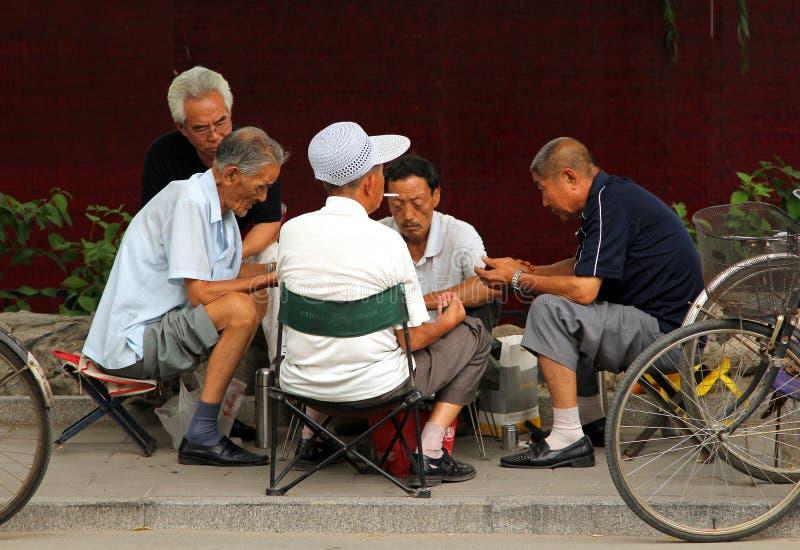 Homens chineses que jogam o mahjong ou o majiang, jogo chinês muito popular no parque de Jingshan, não longe da Cidade Proibida imagem de stock