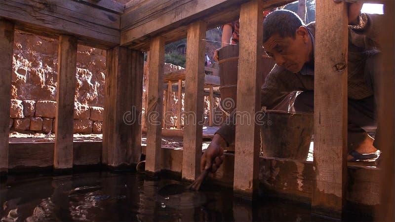 Homens chineses que trabalham no campo de sal Use a salmoura para o processo de cozimento de sal yunnan China foto de stock royalty free