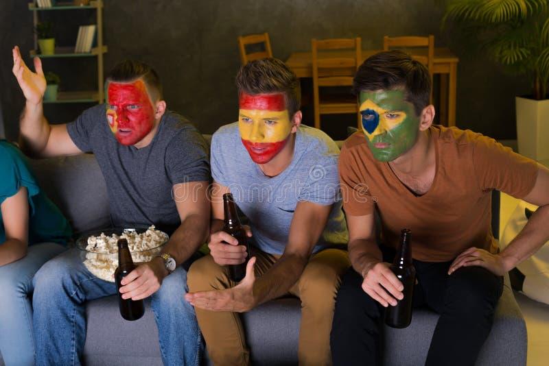 Homens com as caras coloridas do futebol fotos de stock royalty free