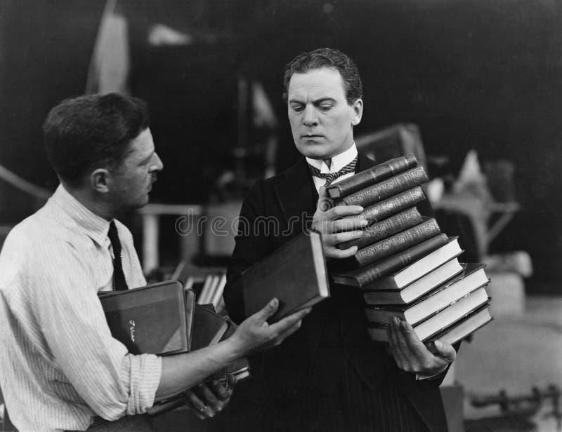 Homens com as pilhas de livros (todas as pessoas descritas não são umas vivas mais longo e nenhuma propriedade existe Garantias d foto de stock royalty free