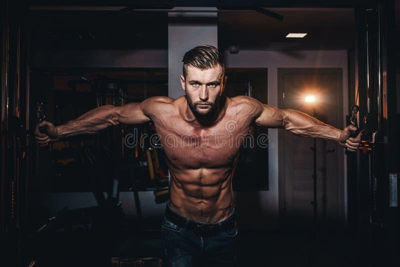 Homens consideráveis do halterofilista muscular que fazem exercícios no gym com torso despido Indivíduo atlético forte com múscul imagem de stock