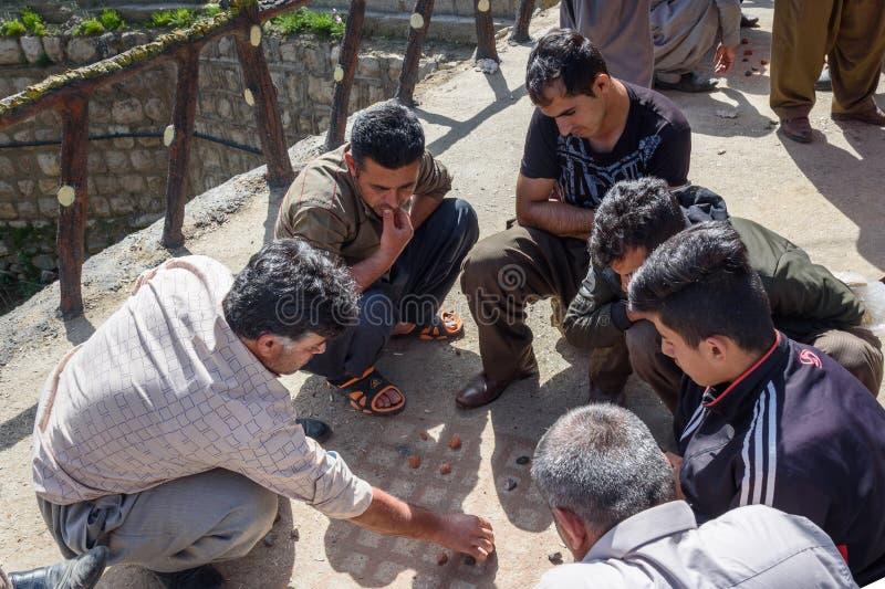 Homens curdos que jogam o jogo tradicional com as pedras pequenas nas ruas na vila de Darreh Tafi perto do lago Zarivar, Irã fotos de stock royalty free