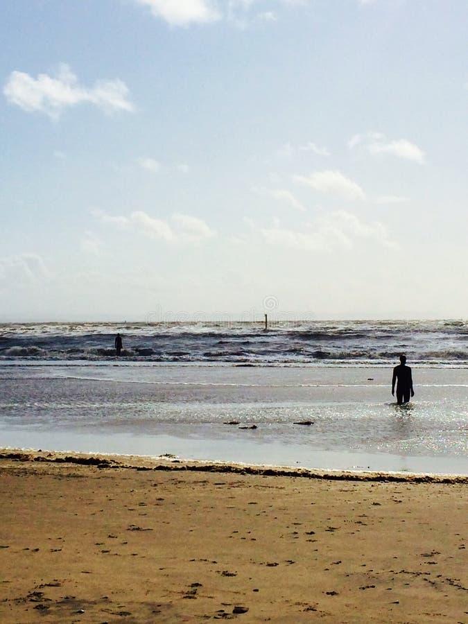 Homens de bronze que olham para fora ao mar foto de stock