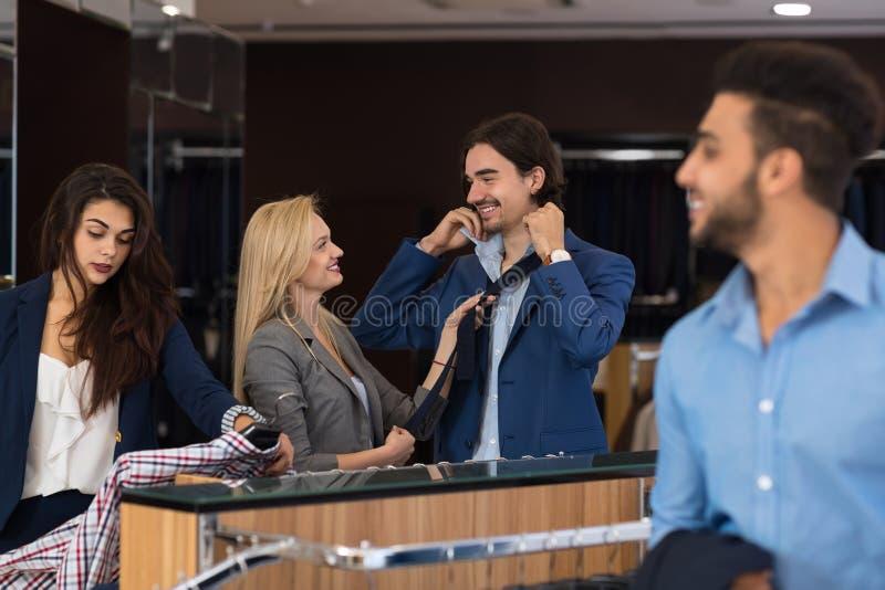 Homens de negócio bem sucedidos que compram a roupa nova na loja moderna dos ternos, ajuda fêmea dos assistentes fotos de stock
