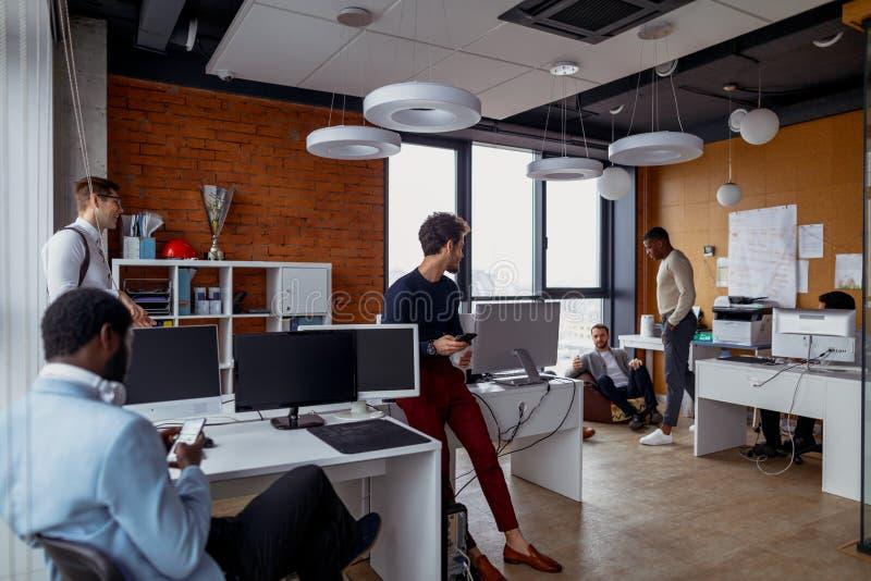 Homens de negócio em um interior do escritório do espaço aberto com uma janela panorâmico, possibilidade remota fotografia de stock
