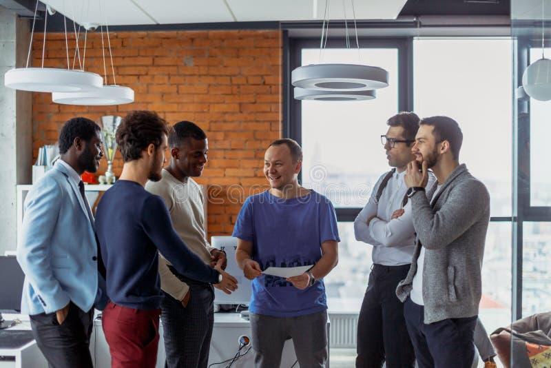 Homens de negócio em um interior do escritório do espaço aberto com uma janela panorâmico, possibilidade remota foto de stock