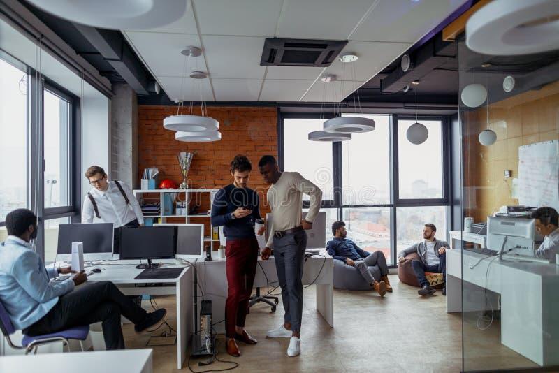 Homens de negócio em um interior do escritório do espaço aberto com uma janela panorâmico, possibilidade remota fotografia de stock royalty free