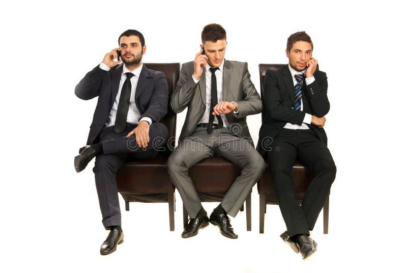 Homens de negócio que falam por telefones imagens de stock
