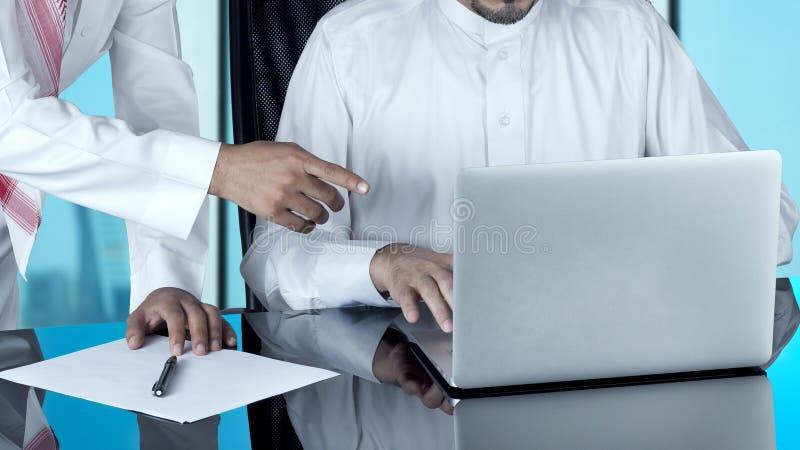 Homens de negócios árabes que trabalham em um portátil imagens de stock