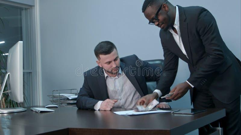 Homens de negócios afro-americanos que contam o dinheiro na mesa e que dão contas a seu sócio caucasiano, elas que agitam as mãos fotografia de stock royalty free