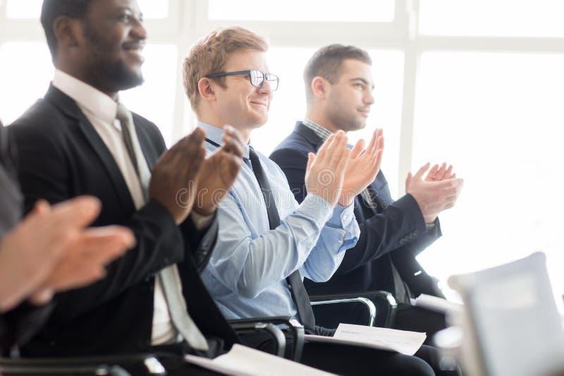 Homens de negócios de aplauso na reunião foto de stock