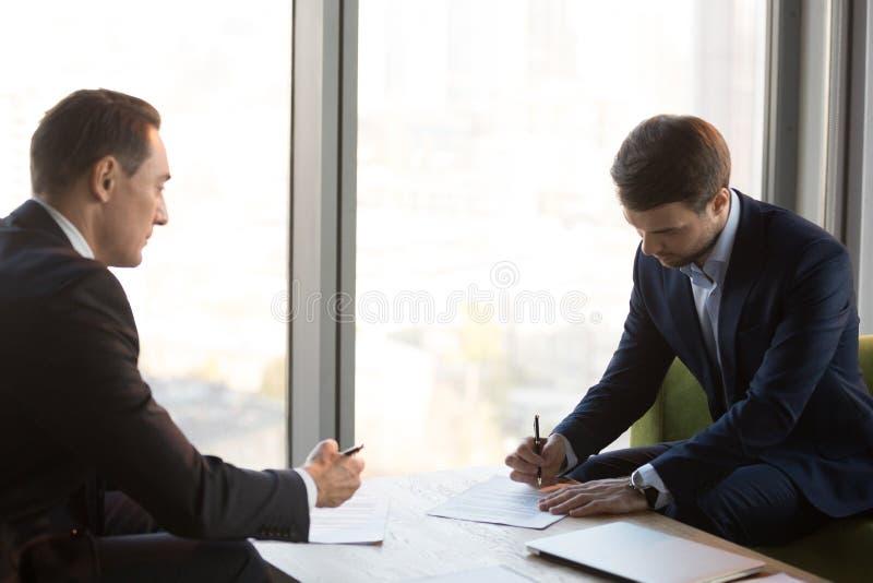 Homens de negócios bem vestidos que assinam o contrato durante o meetin do negócio fotografia de stock