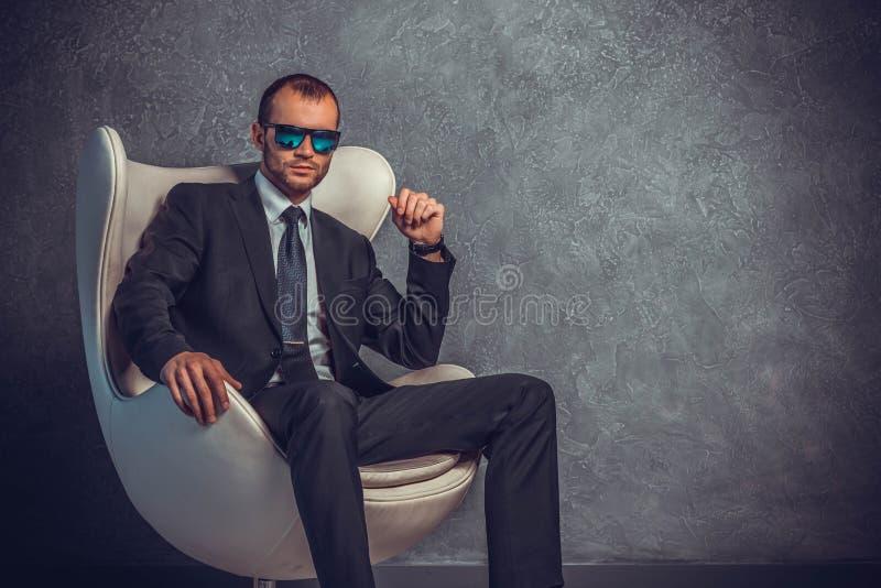 Homens de negócios brutais no terno com laço e óculos de sol que sentam-se na cadeira imagem de stock royalty free