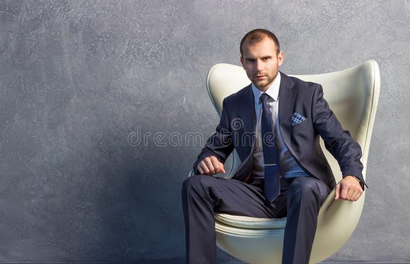 Homens de negócios brutais no terno com o laço que senta-se na cadeira foto de stock royalty free